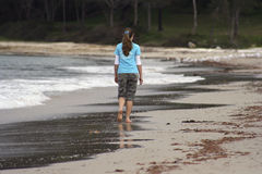 Girl walking on the beach Stock Photography