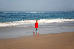 Girl walking on beach Stock Photography