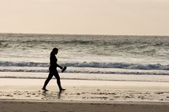 Girl walking on the Beach. A girl in a wetsuit walks along the beach at sunset Stock Image