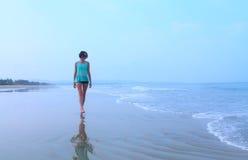 Girl walking on the beach Stock Photos