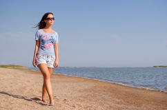 Girl walking on the beach. Girl with black glasses walking on the beach stock images