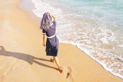 Girl walking on beach near the sea. stock photo