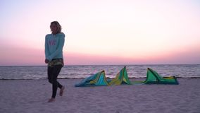 A woman in a suit for diving at dawn walks along the beach past training kites. The girl is walking the beach, next to the sand lie training kites stock video