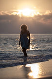 Girl is walking on the beach during the sunrise Royalty Free Stock Images