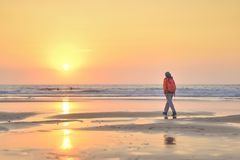 Girl walking on beach at sunset. stock images