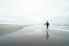 Girl walking on the beach in winter Stock Photography