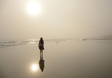 Girl walking on beautiful foggy beach. Stock Images