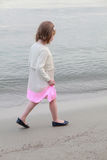 Girl walking with black ballet on the beach Stock Photography