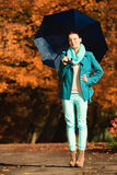 Girl walking with blue umbrella in autumnal park Royalty Free Stock Photo