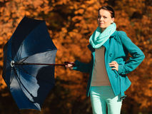 Girl walking with blue umbrella in autumnal park Stock Photography