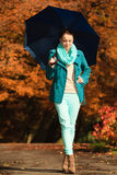 Girl walking with blue umbrella in autumnal park Stock Photos