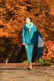 Girl walking with blue umbrella in autumnal park Stock Images