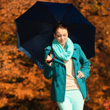 Girl walking with blue umbrella in autumnal park Royalty Free Stock Images