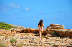 Girl walking camouflaged with landscape rocky beach in Ibiza, girl freedom royalty free stock images