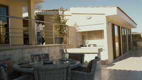 The girl walking from the car to the villa terrace. The girl is walking along the terrace of the house near the dinner table. The served table is on the stock footage