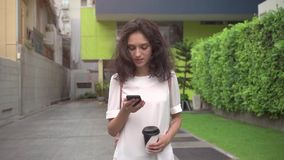 Girl walking on city streets and drinking coffee to go in super slow motion. Portrait of young attractive businesswoman drinking coffee to go on a break and stock video