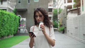 Girl walking on city streets and drinking coffee to go in super slow motion. Portrait of young attractive businesswoman drinking coffee to go on a break and stock video footage