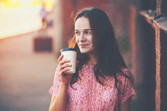 Girl walking with coffee. Smiling pretty girl walking in street with morning coffee royalty free stock photography