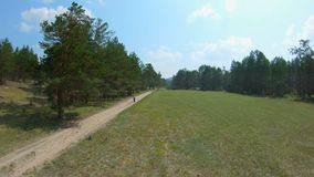 Girl walking on a country road. Aerial shot. Drone flies back past a woman stock video footage