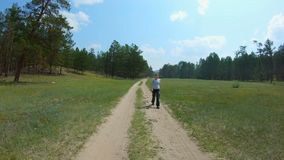Girl walking on a country road. Slow motion stock video footage
