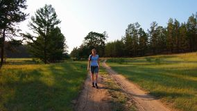 Girl walking on a country road at sunset. Slow motion stock video footage