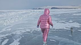 Girl walking on cracked ice of a frozen lake Baikal. Woman traveler explores and looks at an ice floe. It is magical stock footage
