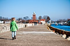 Girl walking on Darlowo jetty. A five year old girl walking alone on Darlowo (Poland) jetty or pier towards the lighthouse Stock Photo