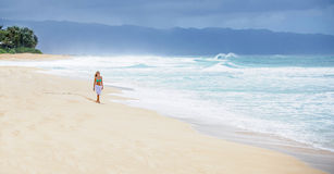 Girl walking on deserted beach. A beautiful girl blonde girl in a bikini walking on deserted beach Stock Photo