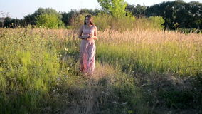 Girl walking on a dirt road, grassy stock footage