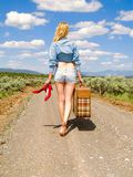 Girl walking on a dirt road with a suitcase. Carrying her red shoes Stock Photography