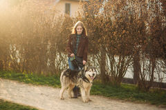 A girl is walking with a dog along the embankment. Beautiful Husky dog. The river. Spring. Stock Image