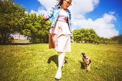 A girl is walking with a dog in the park. stock images