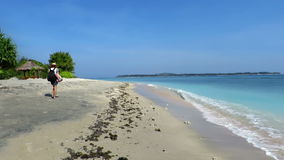 Girl walking down beautiful sandy beach stock video