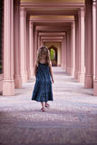 Girl walking down corridor in old Palace Garden Stock Images