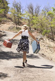 Girl Walking Down Path. Girl walking down road carrying suitcases royalty free stock photos