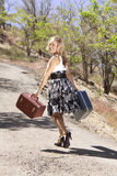 Girl Walking Down Path Looking Over Her Shoulder. Girl walking down road carrying suitcases and looking back over her shoulder Stock Images