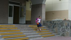 Girl walking down stairs with backpack and flowers bouquet from school door. Back to school concept. summer day hanheld stock footage