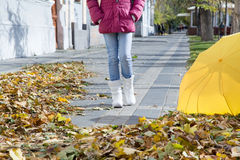 Girl walking down the street with autumn leaves. Girl walking street in the autumn on a warm sunny day Royalty Free Stock Images