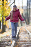 Girl walking down train tracks Stock Image