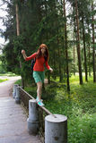 Girl walking on fence. Happy girl walking on the fence in a park Stock Photography