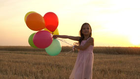 Girl walking in a field with balloons Stock Photo