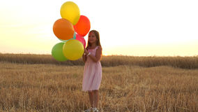 Girl walking in a field with balloons Royalty Free Stock Image