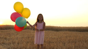 Girl walking in a field with balloons Royalty Free Stock Photos
