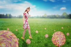 Girl walking on field with colorful candies. Royalty Free Stock Photo