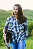Girl walking in the field with a guitar in hand Royalty Free Stock Image