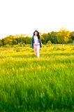 Girl walking in a field Stock Photography