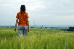 Girl walking in field overlooking valley Stock Photos