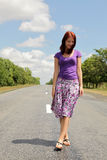 Girl walking by foot on road Stock Images