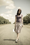 Girl walking by foot on road in vintage style Stock Image