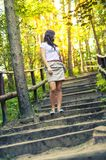 Girl walking through the forest pathway Stock Image